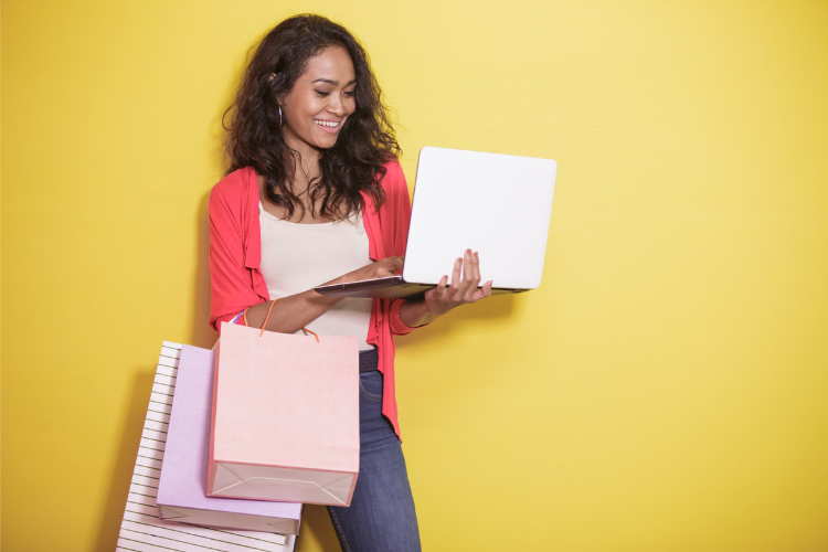 Woman ecommerce customer browses online shopping sites on a laptop while holding three shopping bags