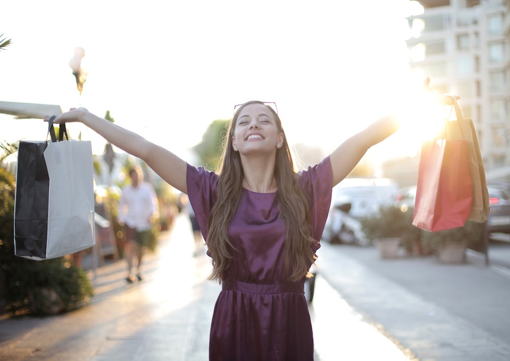 Happy woman shopper holds up shopping bags