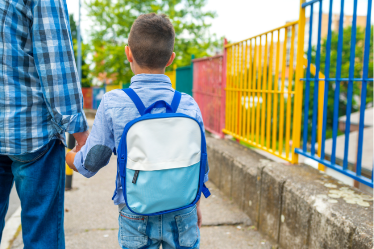 Child walking to school with parent with new backpack and clothes from back-to-school shopping