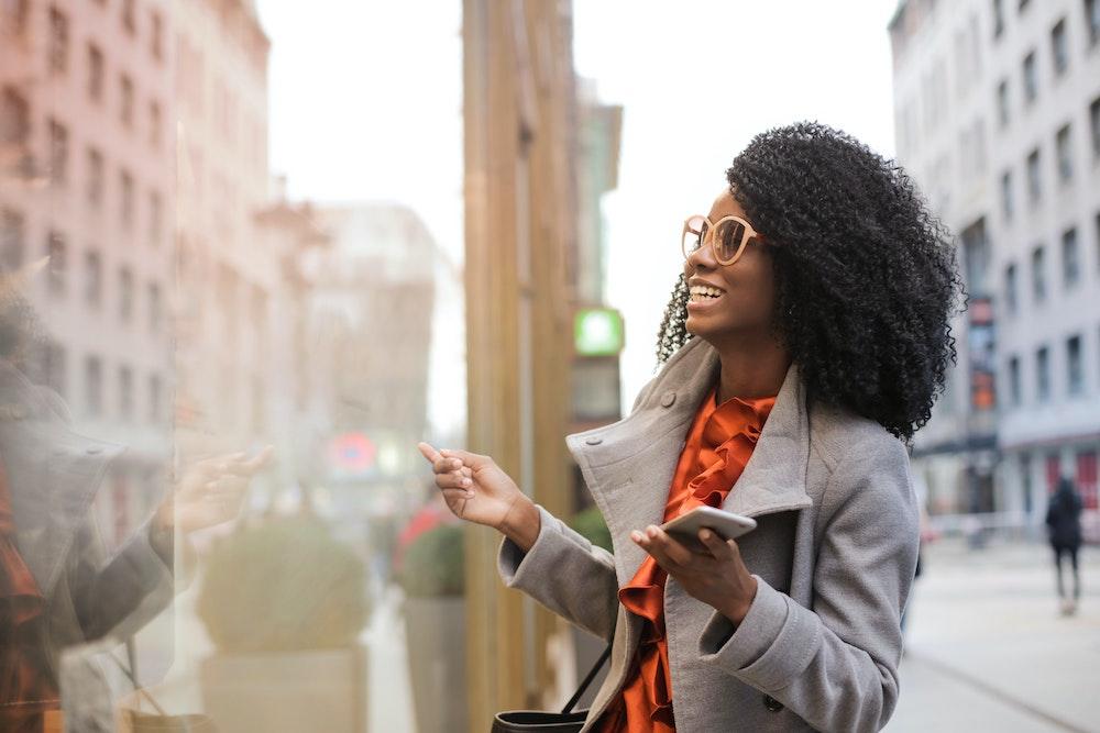 Happy customer looks in store window
