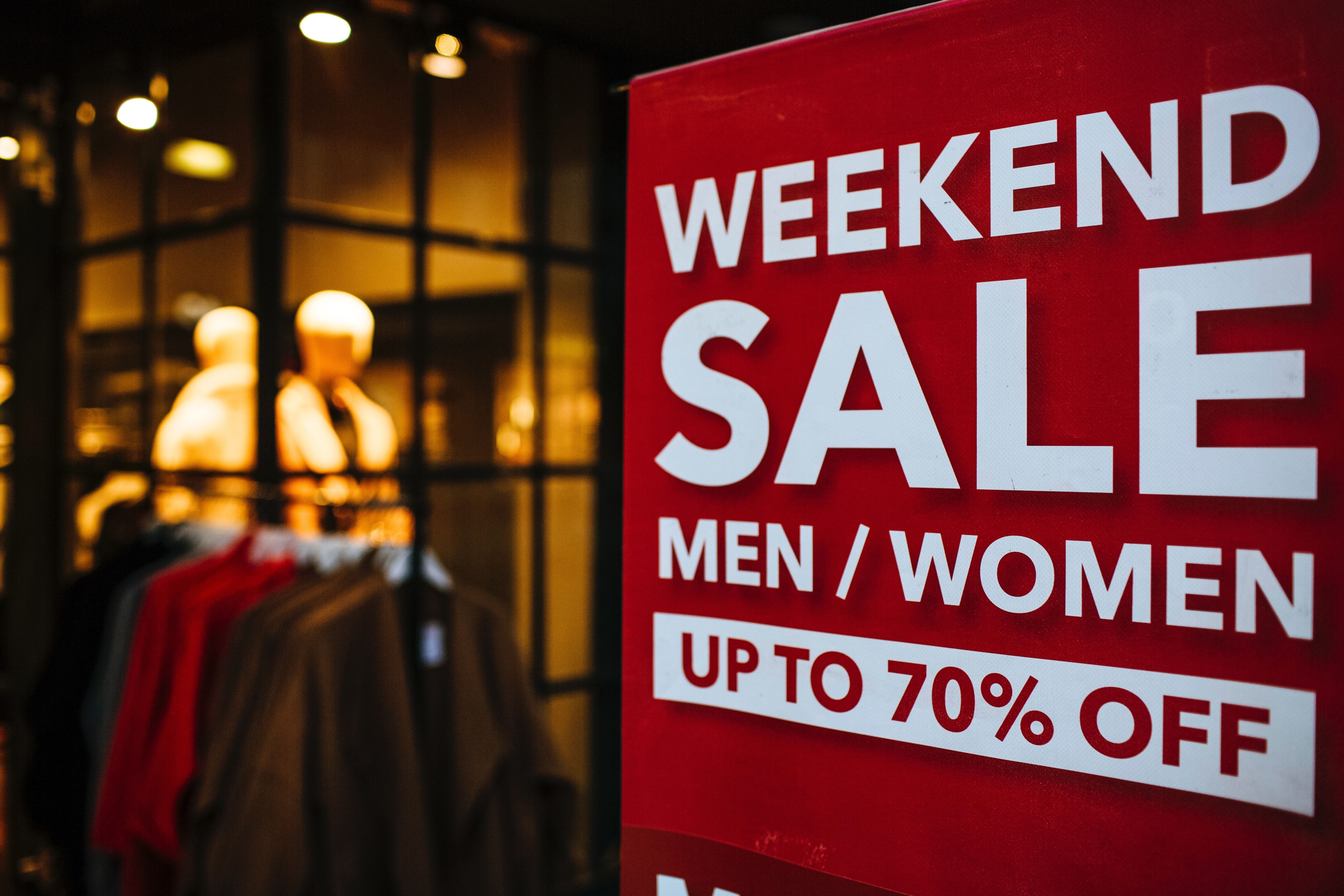Shopping sale sign outside a store window with labor day weekend discounts
