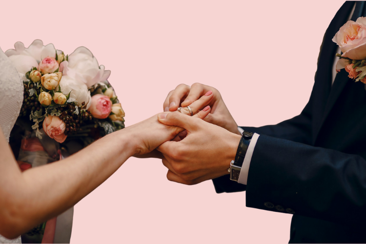 Close-up on the hands of a woman and man exchanging wedding rings